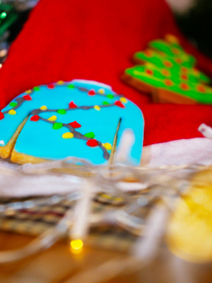 A blue Christmas sweater cookie with lights on it and a Christmas tree cookie on a Christmas stocking