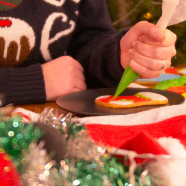 Decorating a cookie with Christmas decorations around